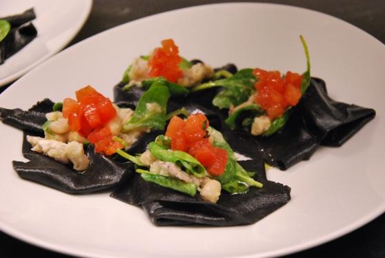 Raviolo nero aperto ripieno di insalatina di cicale di mare, pomodori e spinacetti